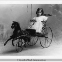 1900s: Child seated in toy cart
